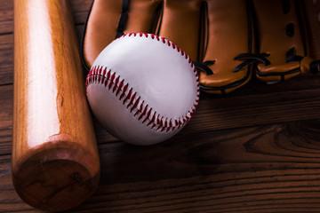Baseball bat, ball and glove wooden table. Closeup