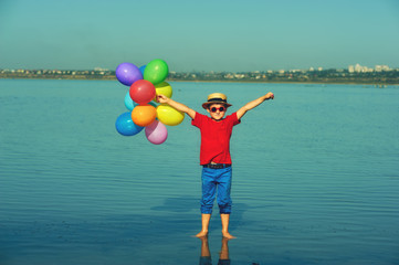 Happy child having fun in nature in summer. Boy with balloons in nature .