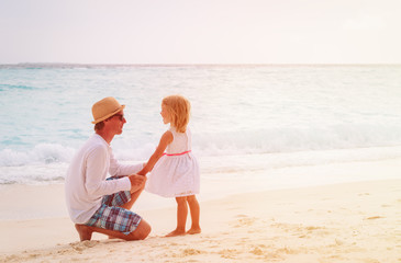 father and little daughter holding hands on beach