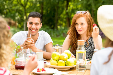 Smiling red-haired woman and spanish man enjoying outdoor party