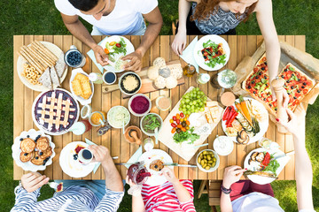 Top view on wooden table with pastry, pizza and fruits during garden party