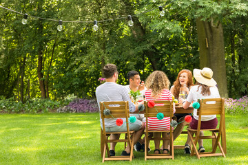 Friends enjoying meeting during birthday party in the garden