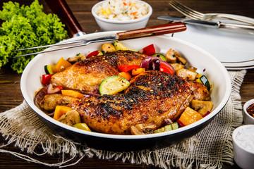 Roast chicken legs served on frying pan