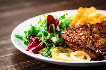 Grilled beefsteak with french fries and vegetable salad