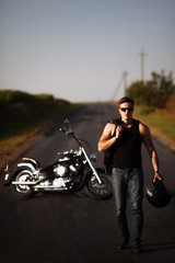 Handsome confident biker man in glasses posing at his motorcycle. Countryside road background
