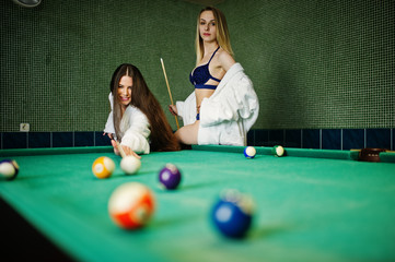 Two sexy girls in white bathrobe and swimsuit play pool billiards.