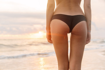 Fitness girl ass. Close up of buttocks of pretty girl in sexy bikini stay in front of the water. Fit lady on sand sea beach sunset or ocean sunrise. Travel, active, surfing, freedom lifestyle concept.