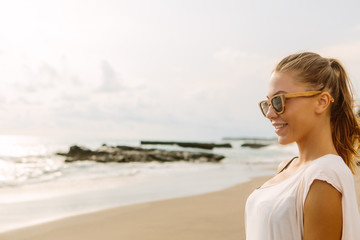 Close up portrait of sexy woman in casual summer dress and wooden sunglasses. Beautiful lady on sea tropic beach sunset or ocean sunrise. Travel, explore, active yoga and meditation lifestyle concept.