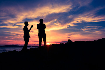 Silhouette two man standing on the clift during sunset