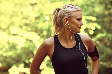 Sporty young woman listening to music before a forest run