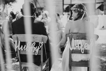 Braut und Bräutigam auf Stühlen bei Outdoor Hochzeit