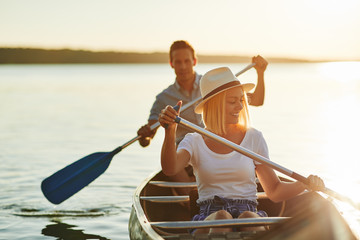 Smiling couple paddling their canoe on a lake in summer
