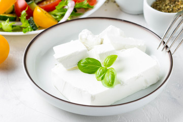 Fresh Greek feta cheese in a bowl whole and slices for salad with vegetables