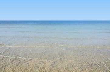 Wall Mural - Calm sea surface near coastline. Seascape in sunny day under clear skies.