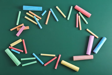 Color pieces of chalk on green background, top view
