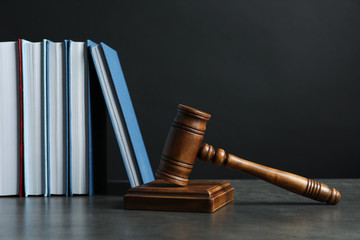Wooden gavel and books on table against dark background. Law concept
