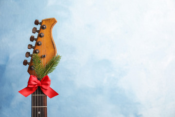 Guitar with bow and fir tree twig on color background. Christmas music concept