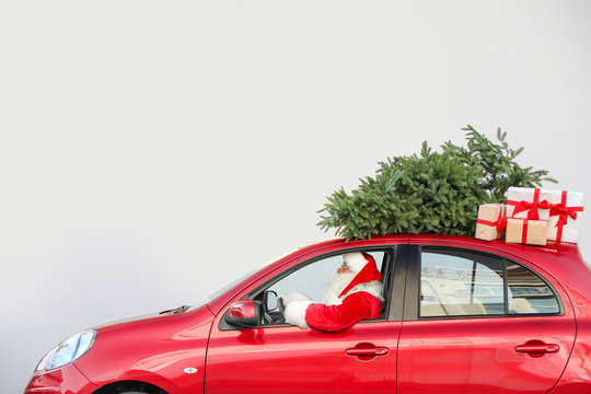 Authentic Santa Claus driving red car with gift boxes and Christmas tree, view from outside