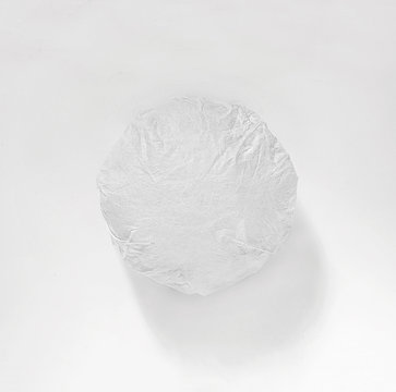 Classic burger packed in the wrapping paper on white background. Top view.