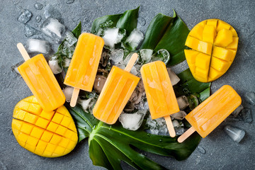 Mango popsicles over green tropical palm leaf on grey stone background. Overhead, top view
