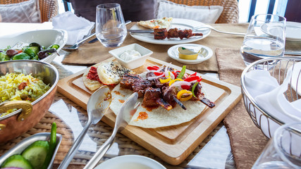 Barbecue grill meat served with vegetables, tortilla and sauce on wooden cutting board. Served table