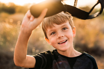 Boy Taking of Hat and Smiling