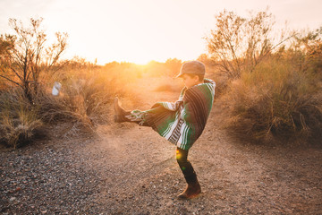 Young Boy Kicking Tin Can in Desert