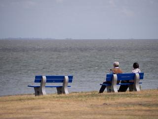 Älteres Paar sitzt auf Bank und schaut auf das Meer