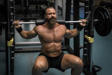 Hombre fuerte con grandes músculos haciendo sentadillas mientras entrena en el gimnasio. Ponerse en forma.