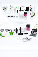 The reflection in the mirror. Creams, perfume bottle and fashion accessories are located on the dressing table.