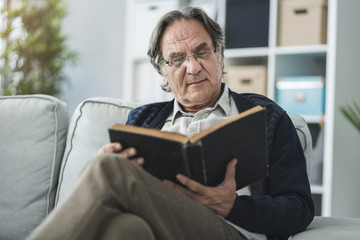Old man reading book at home
