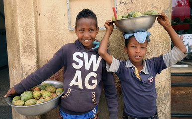 Boys pose for a photograph as they sell cactus fruits along the streets of Asmara