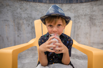 Boy Drinking Water in Chair