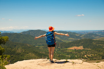 Backpacker adventurer girl admiring the landscape from top of a cliff