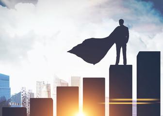 Superman businessman silhouette on bar chart, city