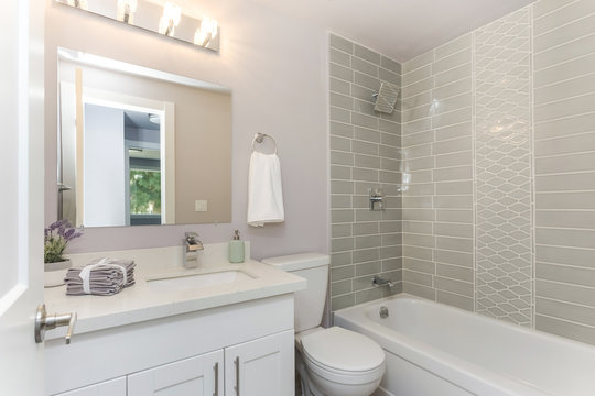 Well designed bathroom with mosaic tiled wall.