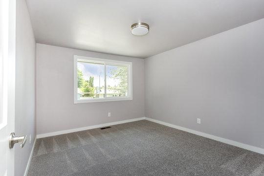 Small empty room with grey carpet floor.