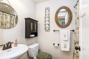 Small bathroom interior with a round pedestal sink and vintage faucet.
