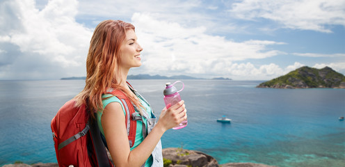 adventure, travel, tourism, hike and people concept - smiling young woman with backpack and bottle of water over background of seychelles island in indian ocean