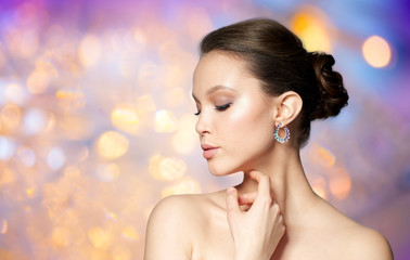 beauty, jewelry, accessories, people and luxury concept - close up of beautiful asian woman face with earring over holidays lights background