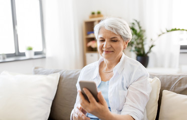 technology, communication and people concept - happy senior woman with smartphone at home