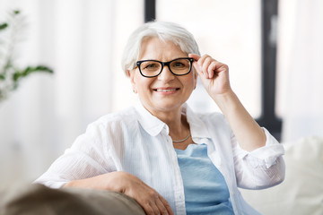 vision, age and people concept - portrait of happy senior woman in glasses sittin on sofa at home