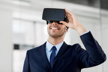 business, technology and augmented reality concept - smiling businessman with vr headset at office