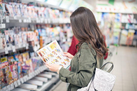 The brunette stands in the Mall near the magazine shelves and looks at the product catalog