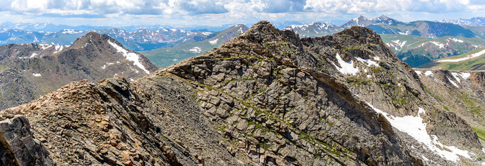 Rugged Mountains - A panoramic spring view of rugged west ridge of Mount Evan, humble Mount Bierstadt, and rolling high peaks of Front Range of Rocky Mountains, seen from summit of Mount Evan. CO, USA