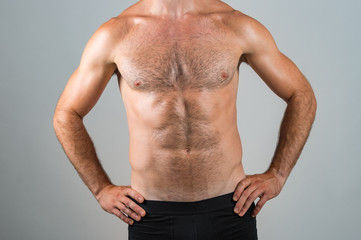 Muscular hairy male chest on grey background.