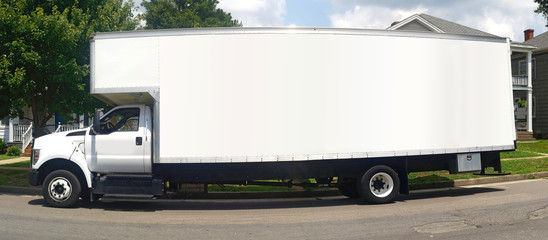 Side view of long white moving van parked on residential street.