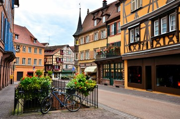 Fototapete - Bicycle in street lined with half timbered buildings, Colmar, Alsace, France