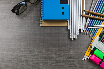 Concept back to school. bags, pencils, books used in classes placed on a wooden floor.