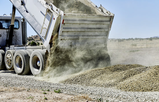 Dump Truck spreading Gravel on Driveway